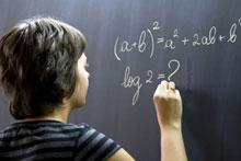 Une fille écrit au tableau dans un cours de maths